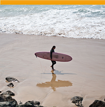 Girl coming out of water with a surfboard in the Basque Country
