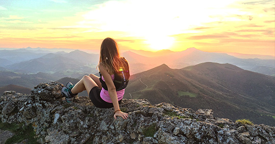 Girl doing a trail at sunset in the Basque Country